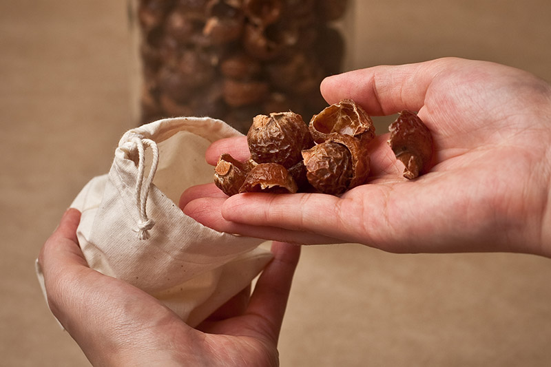 putting soap nuts into cotton wash bag